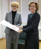 Dr. Meyer receives a large formal certificate from Ambassador Shekerletova while both are standing in the Bulgarian embassy in Berlin.