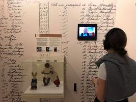Exhibition visitor with back to camera watches and listens to testimony from Holocaust survivor saved through the actions of Sousa Mendes.